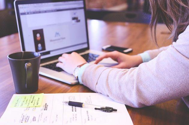 茶色の木のテーブル上でノートパソコンとノートを開いて計画を立てる女性