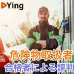 仁王立ちする男性ガソリンスタンド店員とガソリン給油機と車