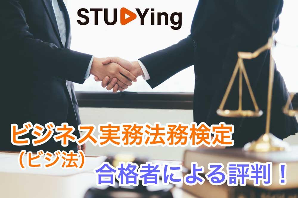 握手するスーツの男性の上半身と手前ある天秤