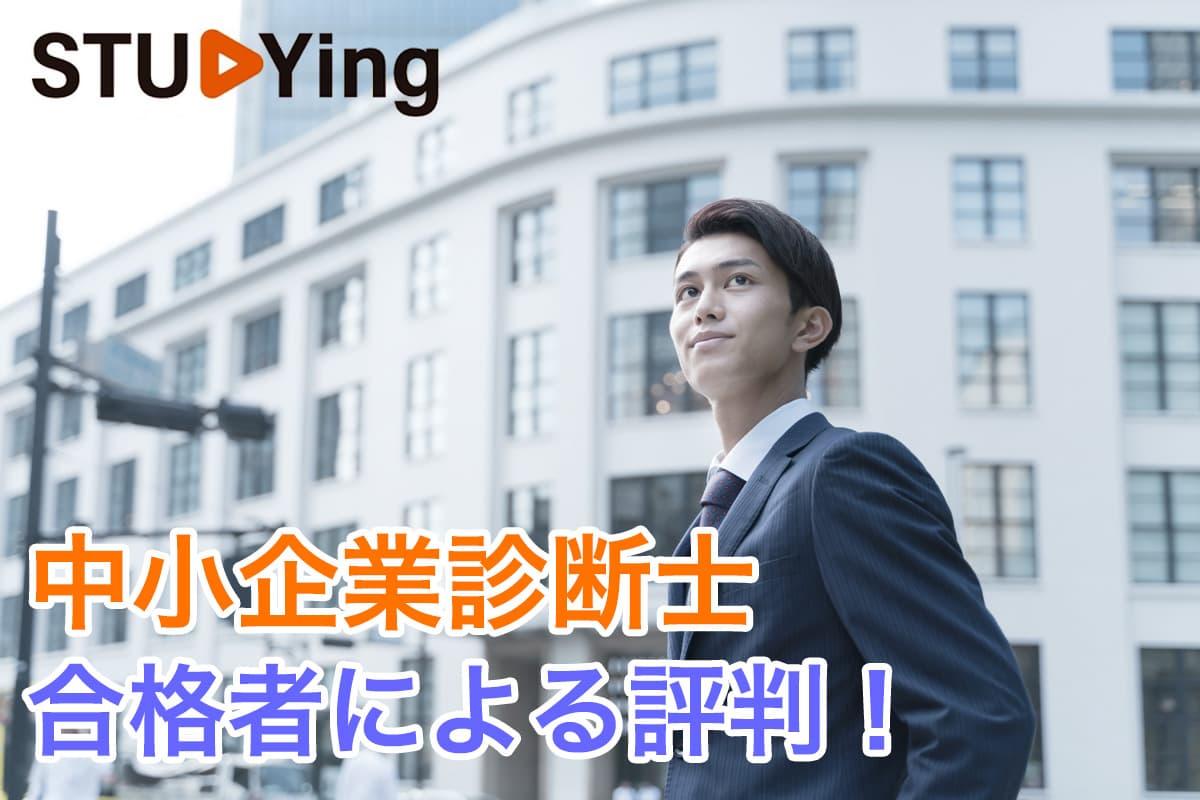 白い低層ビルの手前でポーズをとるスーツ姿の若い男性
